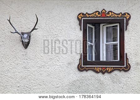 bavarian rural window with typical painted frame decorations and vintage deer antler on old wall