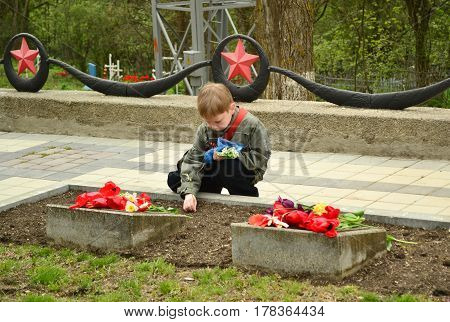 PYATIGORSK RUSSIA - MAY 09 2011: Boy lay flowers to the monument to the fallen soldiers of Second World War Victory Day