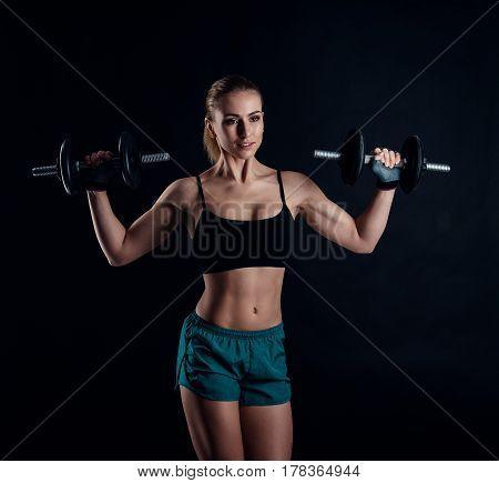 Cute Athletic Model Girl In Sportswear With Dumbbells In Studio Against Black Background. Ideal Fema
