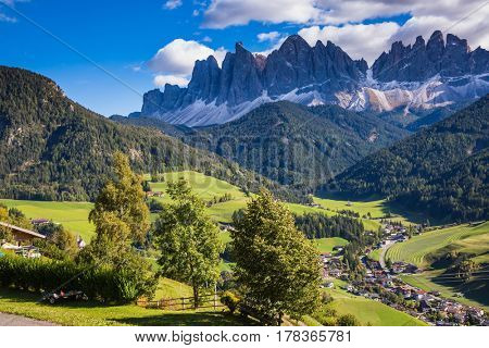 Dolomites, Val de Funes valley. Lovely autumn day. Picturesque mountains surround the green alpine meadows of the valley