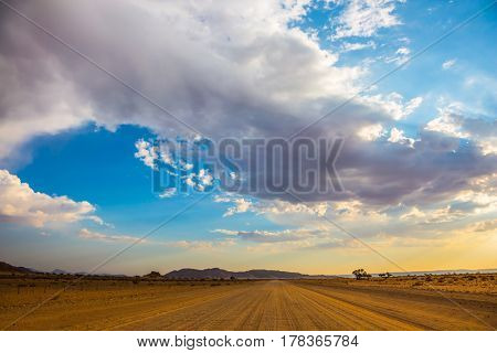 Travel to Namibia, April. Ecotourism in Africa. The wide dirt road in the Namib-Naukluft National Park