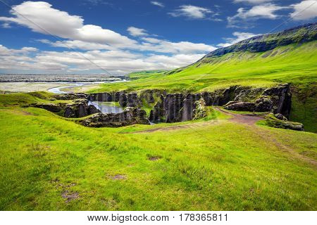 The concept of active northern tourism. The striking canyon in Iceland. Green Tundra in July. Bizarre shape of cliffs surround the stream with glacial water