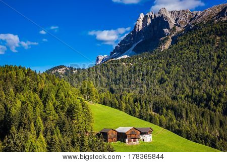 Lovely autumn day. Dolomites, Val de Funes valley. Picturesque mountains surround the green alpine meadows of the valley