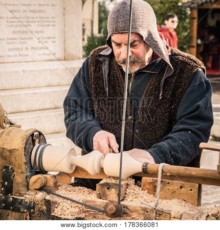 Trento Italy - January 3 2016: An artisan carves a piece of wood using an old manual lathe.