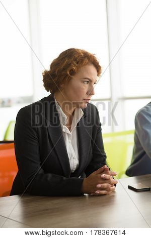 Angry business woman working as boss in building company. Pretty red haired lady going to employ new workers to her company. Aggressive lady looking away.