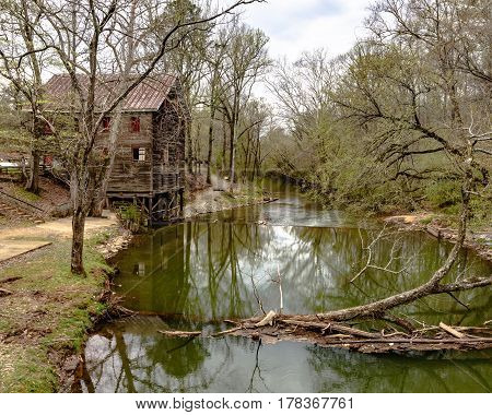 Childersburg Alabama USA - March 25 2017: Kymulga Grist Mill on the banks of Talledega Creek as viewed from the Kymulga Covered Bridge. This structure is orginal to the Civil War period.