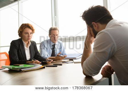 Business representatives of huge company taking interview in one young man. Handsome man sitting in front having stress white interview. Job placement concept.
