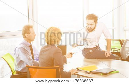 Toned of handsome man sitting on table in office and offering his CV to employees. Business representatives ready to take interview. Business concept.