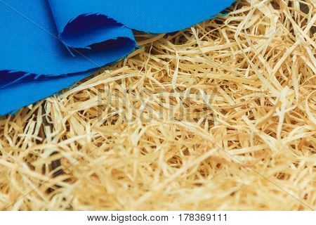 cotton cloth on wooden shavings with copyspace, sewing material.