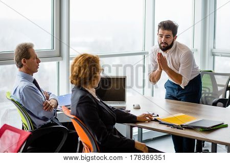 Young man came from India asking employees to offer him job position in company. Handsome man clasped his hands. Employees listening to him.