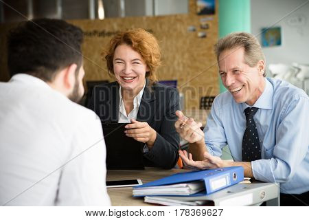Happy smiling HR specialists communicating with young man in office. People asking about previous experience and jobs. Business concept.