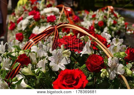 Basket with red rose and lily flowers Saint George ribbon