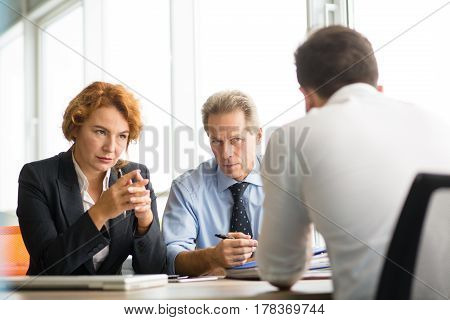 Business people having negotiations with new business partner. Business man and woman looking at man sitting in front. Deal concept. Company partnership concept.