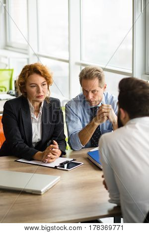 Deal concept. Company partnership concept. Business man and woman looking at man sitting in front. Business people having negotiations with new business partner.