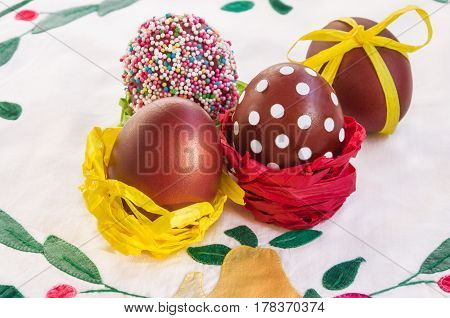 Easter composition in rustic style: colored eggs on napkin with applique work. Main colors: yellow red white. Horizontal.