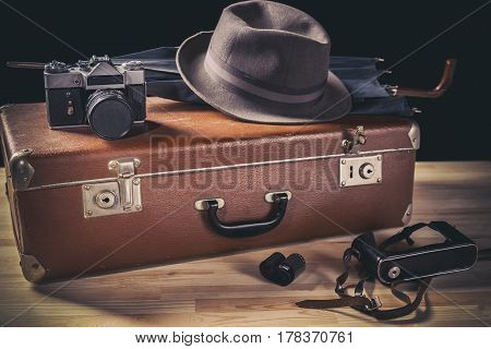 Adventure concept. Old film camera with vintage hat and umbrella on old suitcase neat film and camera case. Vintage toned.