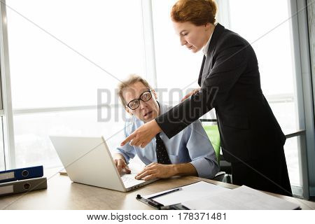 Mobbing, stress, work, scandal concepts. Angry boss woman pointing to laptop computer. Businessman in glasses looking at her hand.