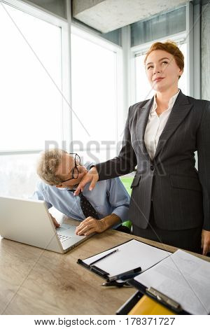 Mobbing, stress, work, scandal concepts. Businessman kissing his boss woman's hand while sitting in front of laptop computer in office.