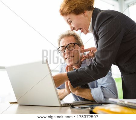 Mobbing, stress, work, scandal concepts. Closeup of angry boss woman screaming and shouting at her worker and pointing to laptop computer.