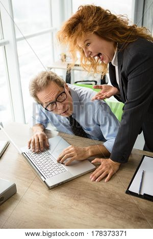 Mobbing, stress, work, scandal concepts. Angry red haired boss woman screaming at her worker in office. Businessman having stress while lying on laptop computer.
