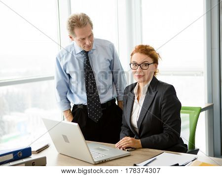 Mobbing, stress, work, scandal concepts. Angry boss man screaming and shouting at his secretary while she is working on laptop computer in office.