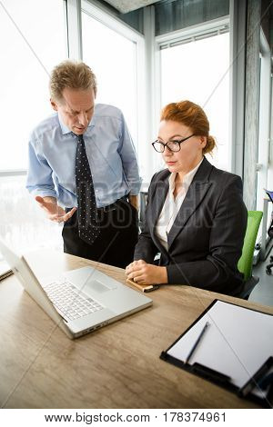 Mobbing, stress, work, scandal concepts. Angry boss man shouting at his worker secretary while she is sitting in front of laptop computer.