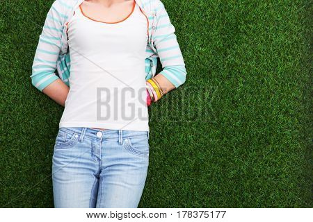 Beautiful young woman lying on green grass