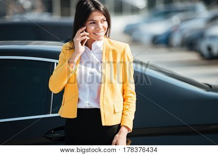 Portrait of a smiling attractive business woman talking on mobile phone while standing at her car outdoors