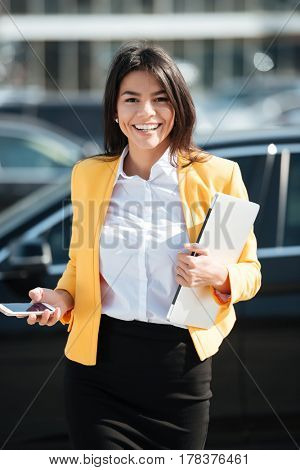 Portrait of a smiling pretty business woman holding mobile phone and laptop while walking outside