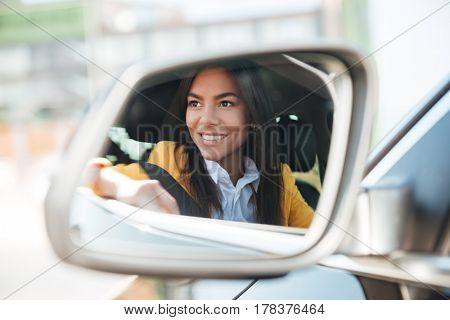 Reflection of smiling business woman in side view car mirror
