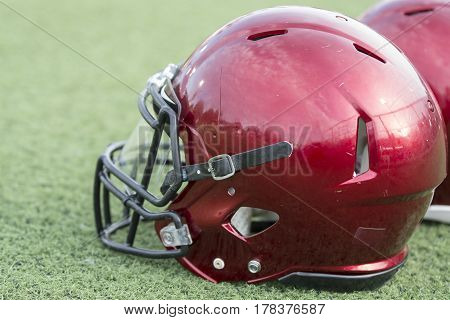 Close up of a red American football helmet sitting on artificial turf