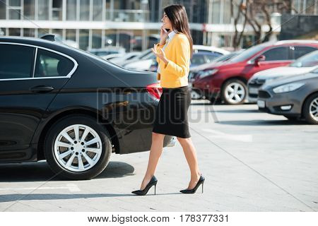 Side view of a young busy business woman walking across the street and talking on mobile phone