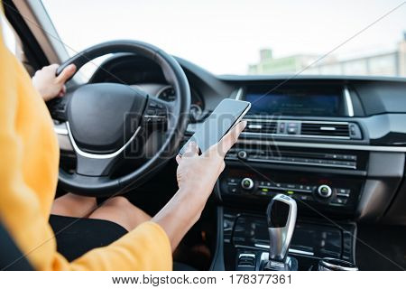 Close up image with female driver and blank phone screen inside a car