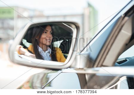 Reflection in side view car mirror of a young woman buying a new car