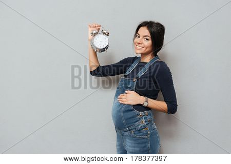 Photo of happy pregnant woman standing and posing while holding watch over grey background. Looking at camera.