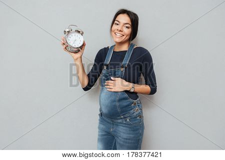 Image of cheerful pregnant woman standing and posing while holding watch over grey background. Looking at camera.