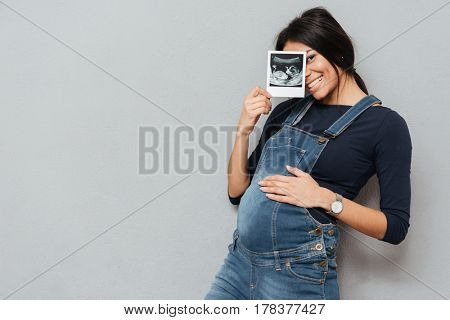Image of pregnant smiling woman standing and posing while showing ultrasound scans over grey background. Looking at camera.