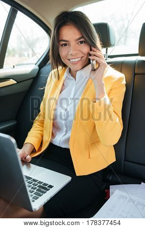 Portrait of a smiling businesswoman traveling to work in car on the back seat with a laptop receiving a phone call
