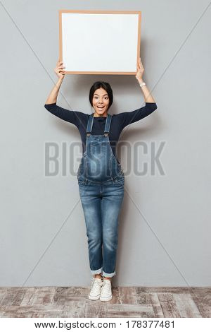 Image of pregnant cheerful woman standing and posing while showing copyspace blank over grey background. Looking at camera.