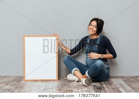 Image of pregnant cheerful woman sitting and posing while showing copyspace blank over grey background. Looking at camera.