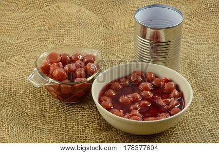 Canned tart pitted cherries in water in white bowl and measuring cup