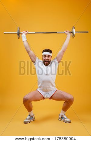 Full length portrait of a fitness man squatting with barbell isolated on a orange background
