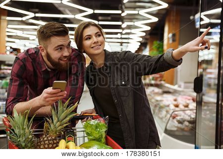 Image of young happy loving couple in supermarket with shopping trolley choosing products. Man holding mobile phone.