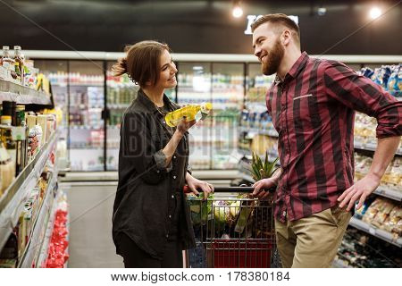 Image of young cheerful loving couple in supermarket with shopping trolley choosing products. Looking aside.