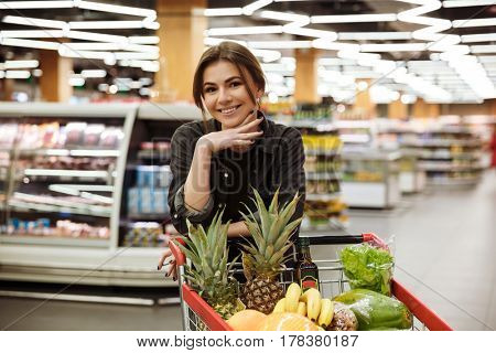 Image of young happy woman in supermarket with shopping trolley choosing products. Looking at camera.