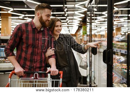 Image of young cheerful loving couple standing in supermarket choosing the products. Looking aside.