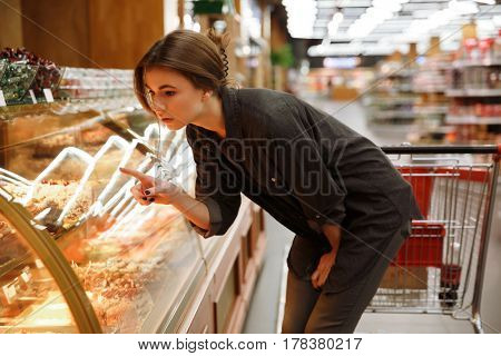 Image of serious woman standing in supermarket choosing pastries. Looking aside.