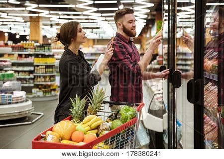 Picture of young cheerful loving couple in supermarket with shopping trolley choosing products. Looking aside.
