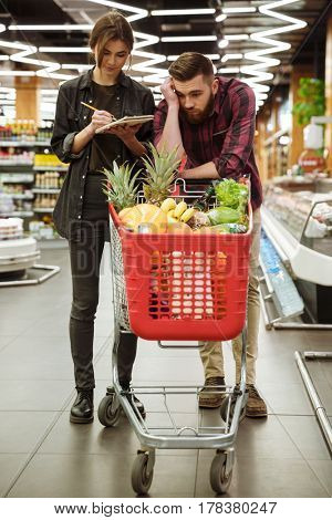 Image of young loving couple in supermarket with shopping trolley choosing products. Tired man looking aside.