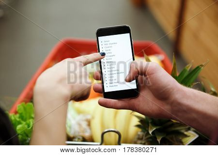 Cropped image of young loving couple standing in supermarket looking at list of purchases in phone.